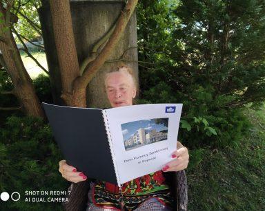Seniorka siedzi w cieniu drzew. W dłoniach ma ulotkę. Na pierwszej stronie budynek i napis: Dom Pomocy Społecznej w Sopocie.
