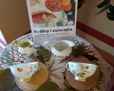 Na stoliku plakat reklamujący wystawę. Obok dekoracja: filiżanki i dzbanuszki na mleko z kwiatowymi wzorami, zielone liście.