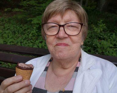 Seniorka siedzi na ławce w lesie. Uśmiecha się, w dłoni trzyma loda.