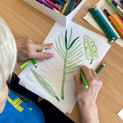 Seniorka pochyla się nad stołem, w dłoni trzyma zielone kredki. Na blacie rozpoczęty rysunek, kolorowe kredki.