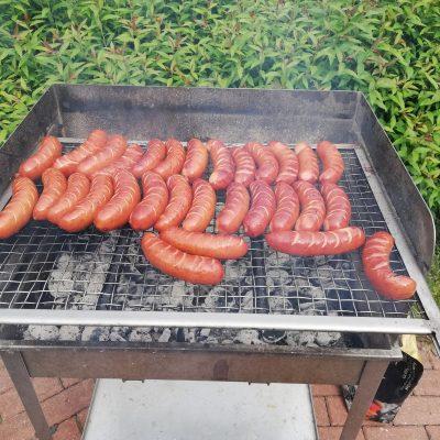 Słoneczny dzień w ogrodzie. Na pierwszym planie grill z piekącymi się kiełbaskami.
