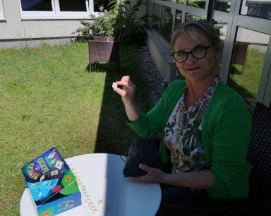 Ogród przed DPS. Uśmiechnięta terapeutka Beata Gadomska przy stoliku. Przed nią pudełko z grą Bingo.