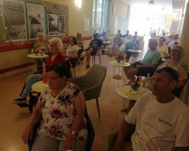 Korytarz. Seniorzy w trakcie wystawy. Siedzą przy stolikach i na kanapach. Na blatach wazony z kolorowymi kwiatami.