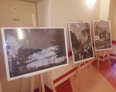 Przy ścianie trzy stelaże. Na każdym czarno-białe zdjęcie z napisem Sopot.