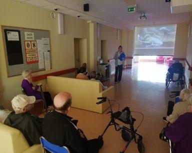 Ciemny korytarz. Seniorzy siedzą przed ekranem projektora, na nim obraz ryb. Obok stoi terapeutka Magdalena Poraj-Górska.