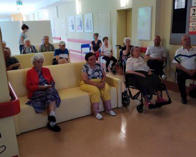 Jasny korytarz. Seniorzy i pracownicy czekają na rozpoczęcie spotkania.