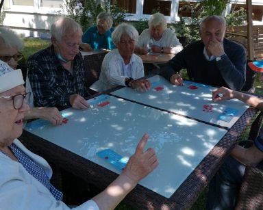 Ogród, drzewa rzucają cień. Seniorzy siedzą przy stołach. Grają w bingo.