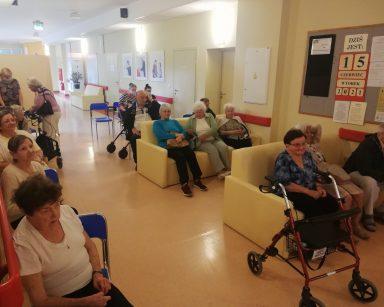 Korytarz. Pracownicy i seniorzy czekają na początek spotkania.