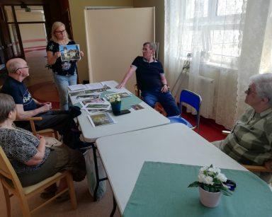 Neurologopedka Anna Szmaja-Wysocka prowadzi zajęcia. Seniorzy przy stołach. Na blatach zdjęcia Sopotu.