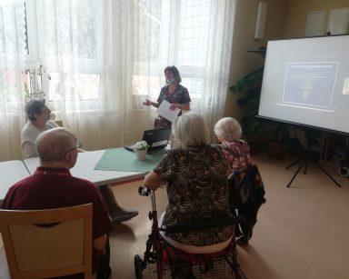 Jasny korytarz. Seniorzy przy stołach. Kierowniczka Ewa Siłakiewicz-Witt prowadzi zajęcia. Za nią ekran projektora.