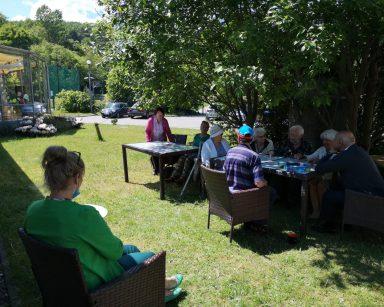 Ogród przed DPS. Seniorzy siedzą w cieniu drzew przy stołach. Grają w bingo. Obok terapeutka Beata Gadomska.