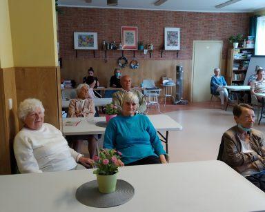 Jasna sala. Seniorzy i pracownicy siedzą przy stołach. Słuchają wykładu.