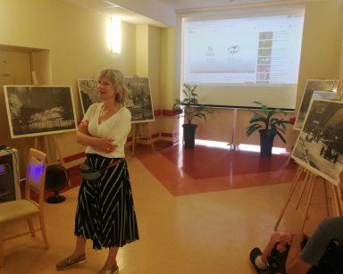 Korytarz. Edukatorka Iwona Zając prowadzi spotkanie. Za nią na stelażach zdjęcia Sopotu, ekran projektora.