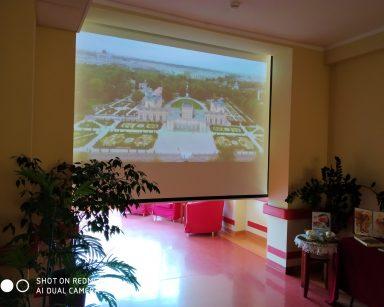 Ciemny korytarz. Ekran projektora. Na nim budynek Muzeum w Wilanowie. Wokół budynku ogrody.