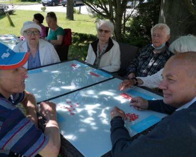 Ogród przed DPS. Seniorzy siedzą w cieniu drzew przy stołach. Grają w bingo.
