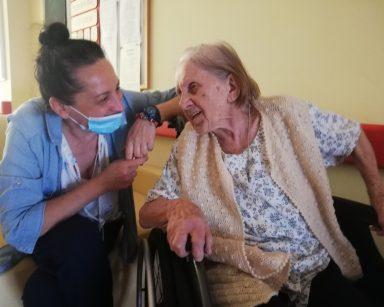 Korytarz. Obok siebie seniorka i terapeutka Magdalena Poraj-Górska. Śmieją się i rozmawiają.