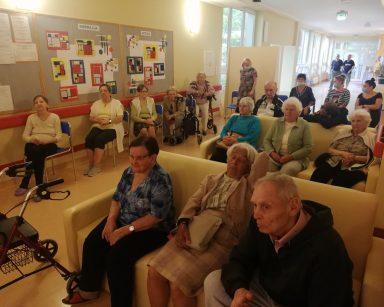 Korytarz. Pracownicy i seniorzy oglądają wystawę.