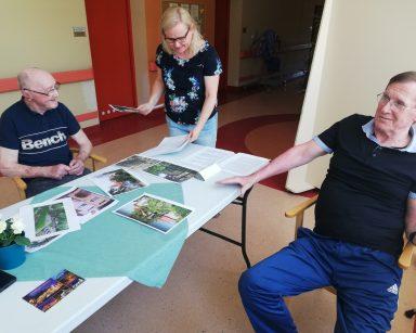Neurologopedka Anna Szmaja-Wysocka prowadzi zajęcia. Przy stole dwaj roześmiani seniorzy.