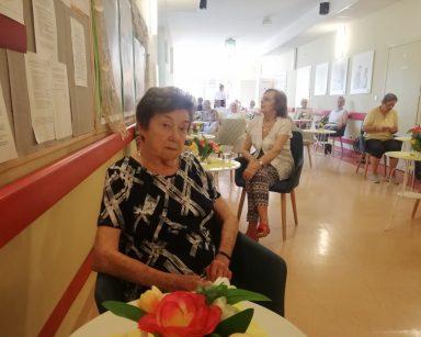Korytarz. Seniorzy uczestniczą w spotkaniu. Siedzą przy stolikach i na kanapach.
