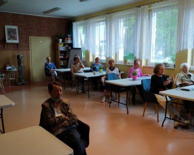 Jasna sala. Seniorzy siedzą przy stołach. Słuchają wykładu.