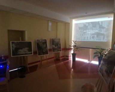 Ciemny korytarz. Ekran projektora, na nim czarno-biały budynek, napis: Architektura Sopotu. Przy ścianach czarno-białe plakaty.