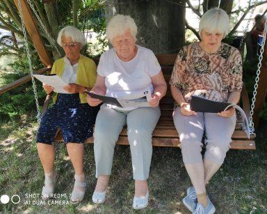 W cieniu, na ogrodowej huśtawce trzy seniorki. W dłoniach trzymają ulotki i czytają.