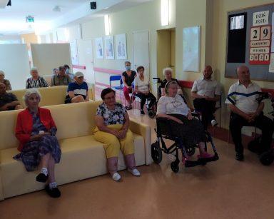 Seniorzy i pracownicy siedzą na kanapach oraz krzesłach. Oglądają wystawę.