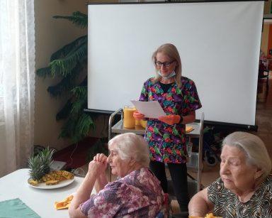 Kierowniczka Ilona Gajewska opowiada seniorom o ananasie. Na stole przed seniorami talerz z plastrami ananasa.