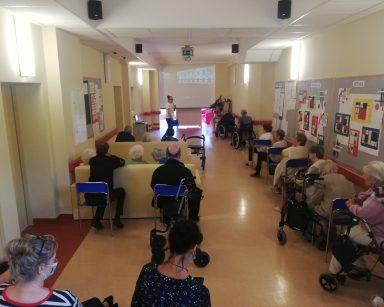 Korytarz. Terapeutka Magdalena Poraj-Górska prowadzi spotkanie. Pracownicy i seniorzy oglądają wystawę na ekranie projektora.