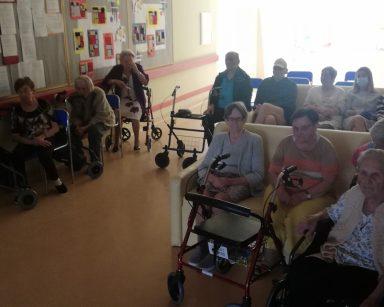 Ciemny korytarz. Seniorzy siedzą i oglądają film.