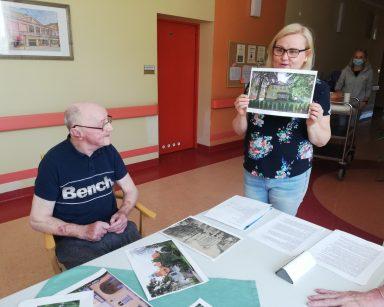 Neurologopedka Anna Szmaja-Wysocka pokazuje zdjęcie budynku. Na blacie kolorowe zdjęcia. Przy stole siedzi senior.
