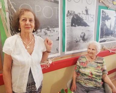 Jasny korytarz. Dwie seniorki. Za nimi na ścianie czarno-białe zdjęcia z napisem Sopot. Dekoracja z sieci rybackiej i muszli.