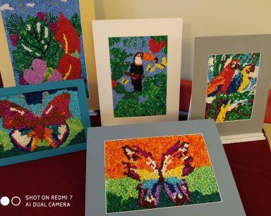 Kolorowe obrazki wykonane z kulek z bibuły. Na nich rośliny i zwierzęta.