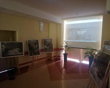 Ciemny korytarz. Ekran projektora, na nim morze, plaża i budynek, napis: Panoramy Sopotu. Przy ścianach czarno-białe plakaty.