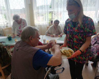 Kierowniczka Ilona Gajewska częstuje seniora ananasem. W tle seniorzy przy stołach. Pija sok anansowy i jedzą ananasa.