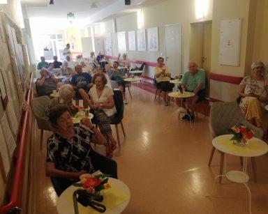 Jasny korytarz. Seniorzy w trakcie spotkania. Siedzą przy stolikach i na kanapach. Na blatach wazony z kolorowymi kwiatami.