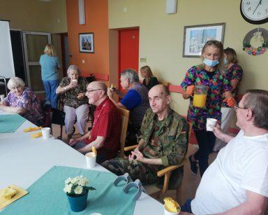 Seniorzy przy stołach jedzą ananasa. Za nimi dyrektorka Agnieszka Cysewska, kierowniczki Ewa Siłakiewicz-Witt i Ilona Gajewska.