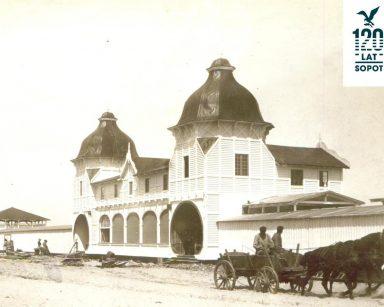 Stara fotografia w kolorze sepii. Drewniany budynek, wóz ciągnięty przez konie. W prawym, górnym rogu napis 120 lat, Sopot.