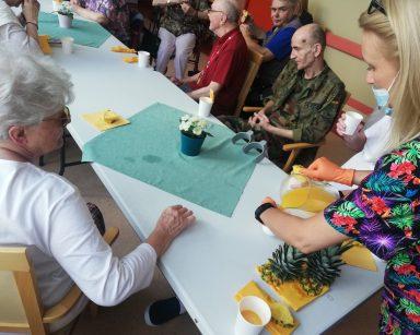 Seniorzy przy stole. Siedzą i kosztują ananasa oraz sok ananasowy. Kierowniczka Ilona Gajewska nalewa sok z dzbanka.