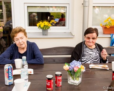 Seniorki siedzą przy stole i rozmawiają. Za nimi budynek DPS, na parapetach żółte bratki.