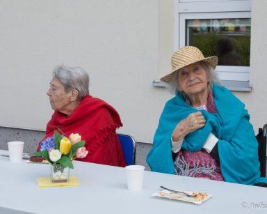 Dwie seniorki przy stoliku. W tle budynek DPS.