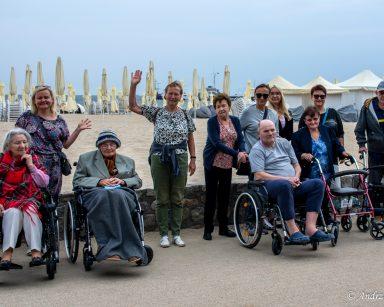 Seniorzy, wolontariusze i pracownicy na świeżym powietrzu. Uśmiechają się i machają. Za nimi plaża i morze.