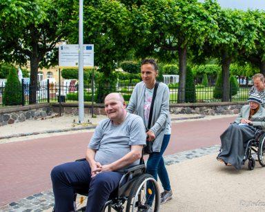 Alejka z drzewami. Dwie wolontariuszki i dwaj seniorzy podczas spaceru.