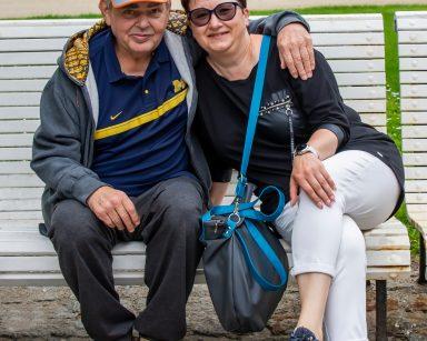 Na białej ławce senior i koordynatorka wolontariatu Edyta Życzyńska. Senior obejmuje ją ręką. W tle zielone krzewy i drzewa.