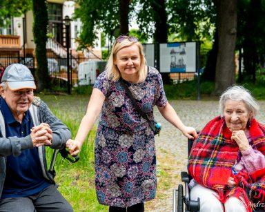 Dwoje seniorów na świeżym powietrzu. Między nimi neurologopedka Anna Szmaja-Wysocka.