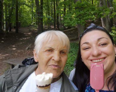 Terapeutka Małgorzata Jancelewicz i seniorka jedzą lody w lesie. Uśmiechają się.