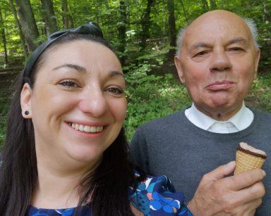 Zielony las. Uśmiechnięci senior i terapeutka Małgorzata Jancelewicz jedzą lody.