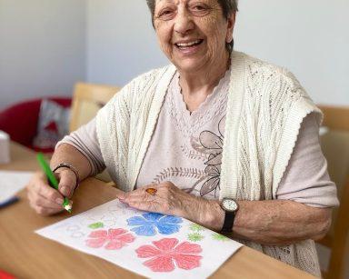 Jasny pokój. Roześmiana seniorka przy stole. W dłoni trzyma kredkę, przed nią na blacie rysunek.