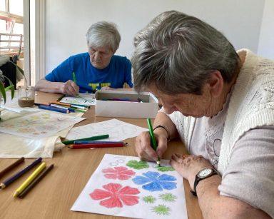 Dwie seniorki przy stole. Są skupione na malowaniu obrazków.