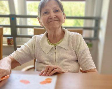 Jasny pokój. Uśmiechnięta seniorka przy stole. W dłoni trzyma kredkę, przed nią na blacie rysunek.